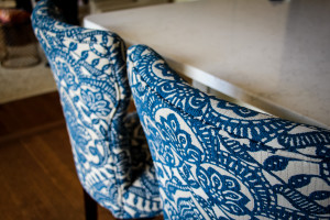 Detail of Custom Upholstered Bar Stools against a white quartz countertop with a blue floral motif.