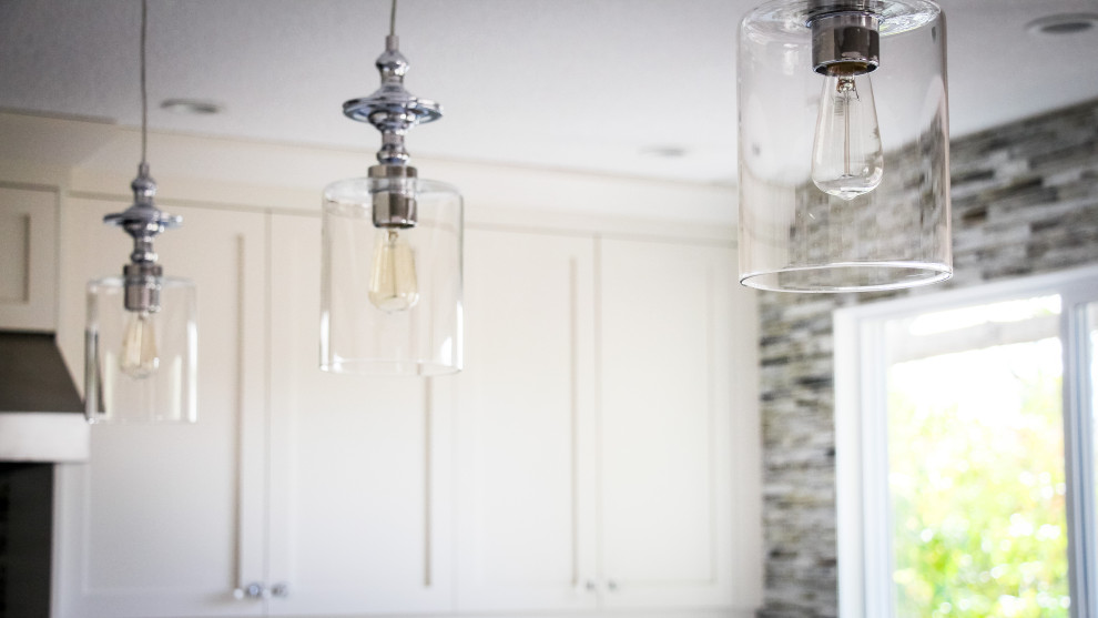 Triplet of pendant lamps over kitchen island with polished chrome hardware and edison bulbs.
