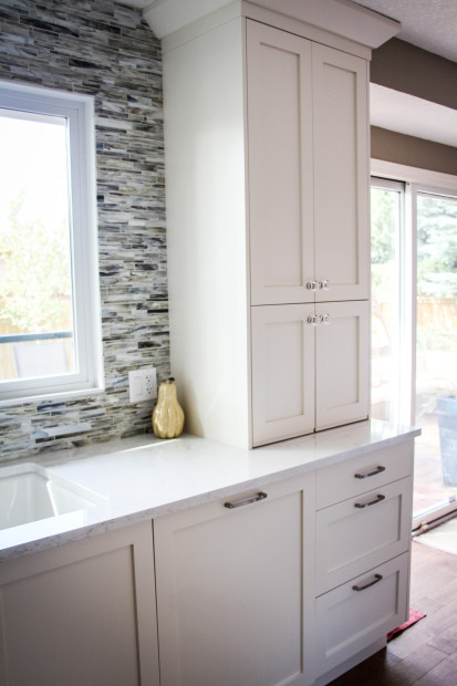 Off-white custom full height cabinetry in a modern shaker style in front of a full height natural stone backsplash