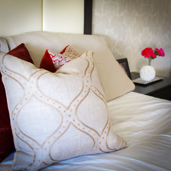 Natural toned pillows with pops of red in a spa-like bedroom retreat