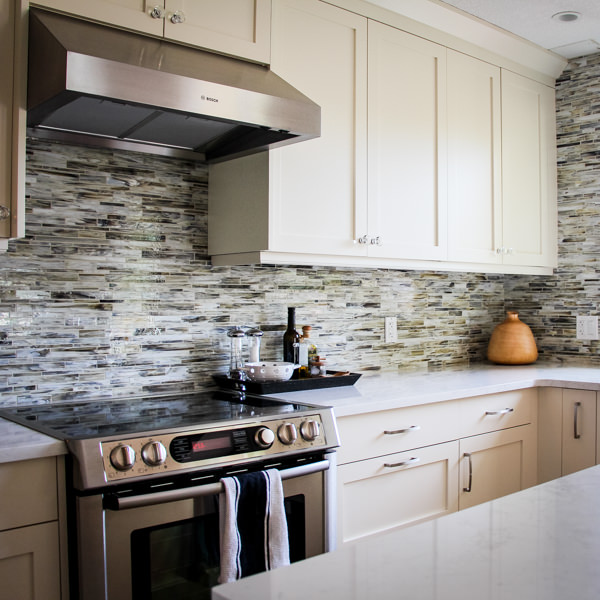 Range with hood shown with full height natural stone backsplash with off white cabinetry.
