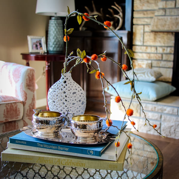 Arrangement of twigs and bugs in a white vase with books on a clustered coffee table grouping.
