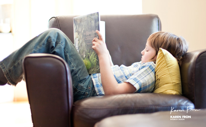 boy reading in brown leather chair enjoying the comforts of home