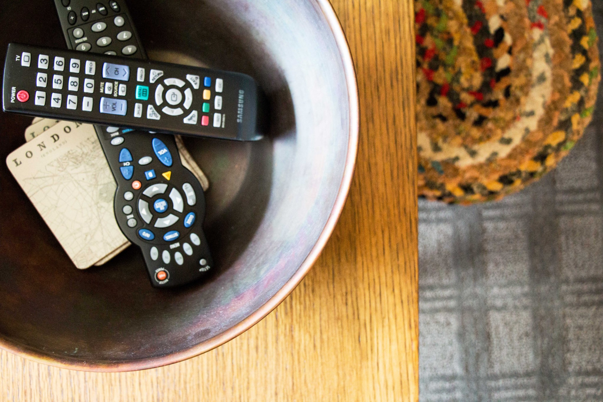 TV remotes stored in a metal bowl on a console table