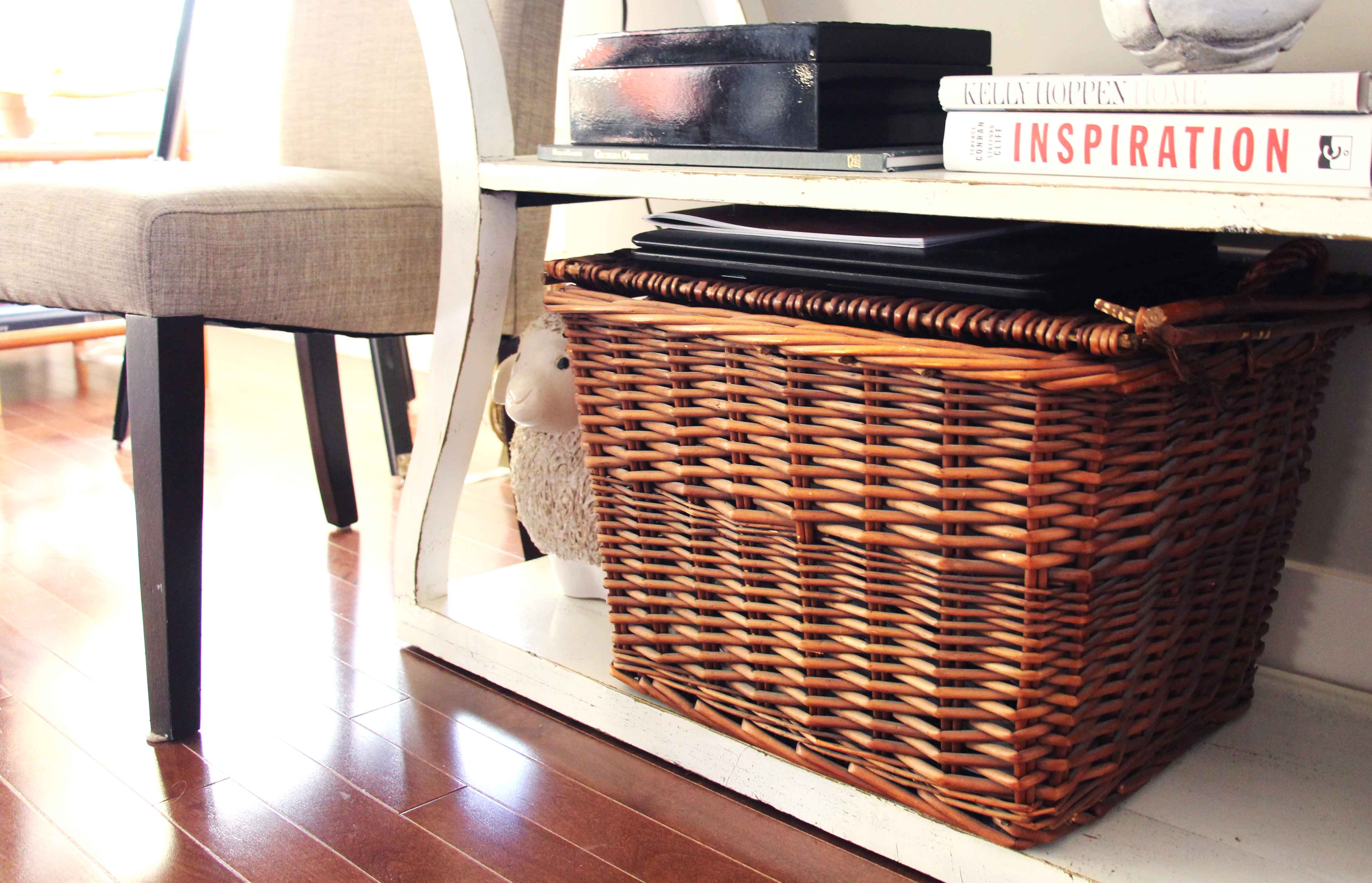 Basket on open white wood shelving with books