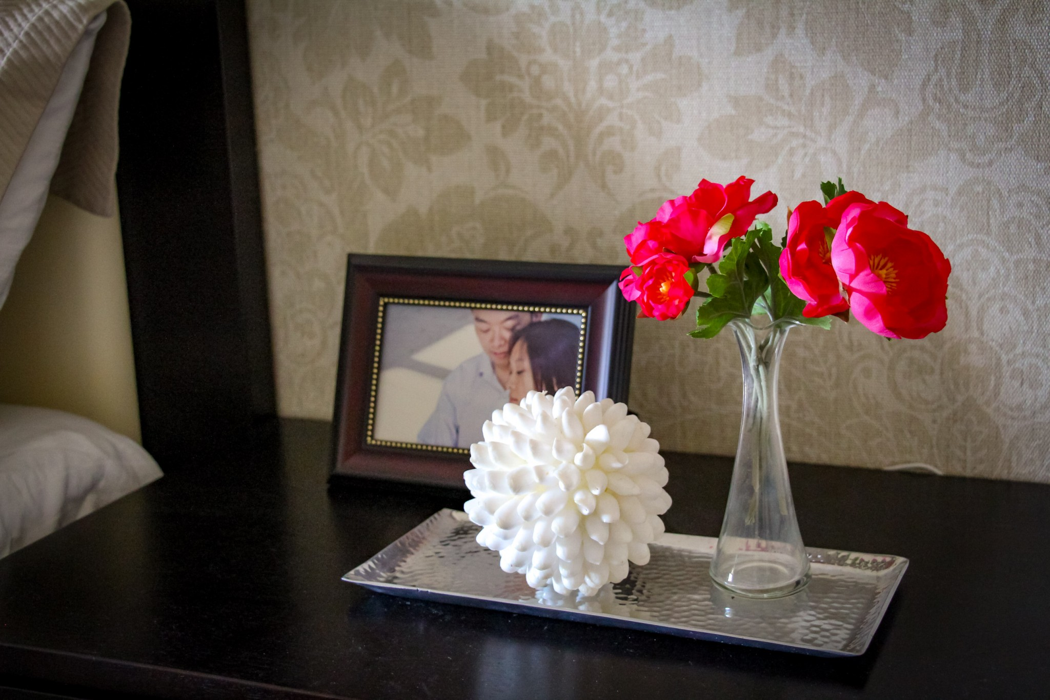 A shell object and fresh flowers on a silver tray arranged in front of a wedding picture in a frame on a couples night table.