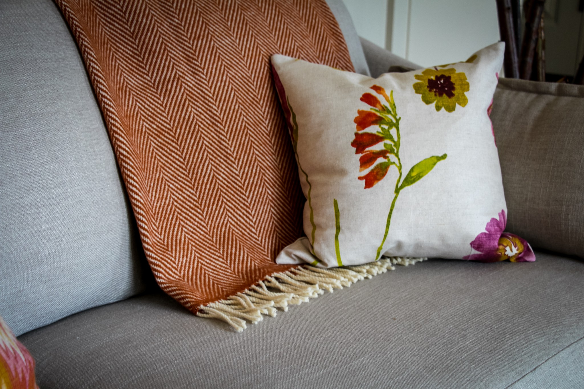 On a neutral gray sofa, a floral pillow offers a pop of seasonal colour.