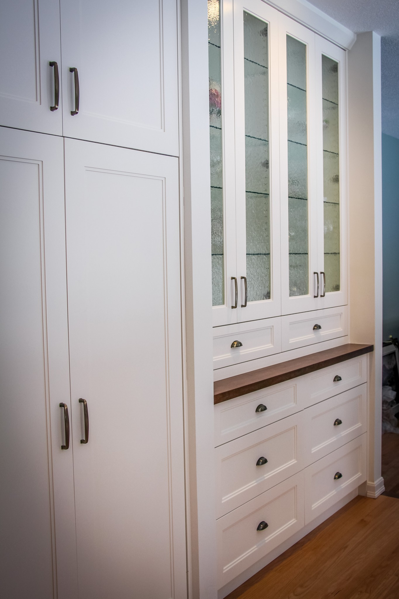 Traditional China storage in a built-in full height cabinet with textured glass doors.