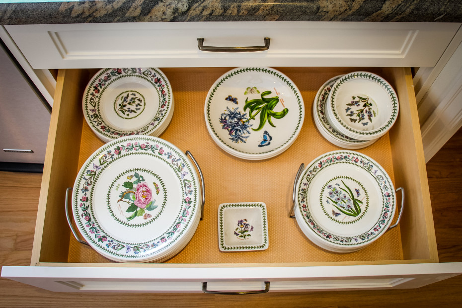 Country floral dinner, salad and dessert plates are stored neatly in a kitchen drawer.