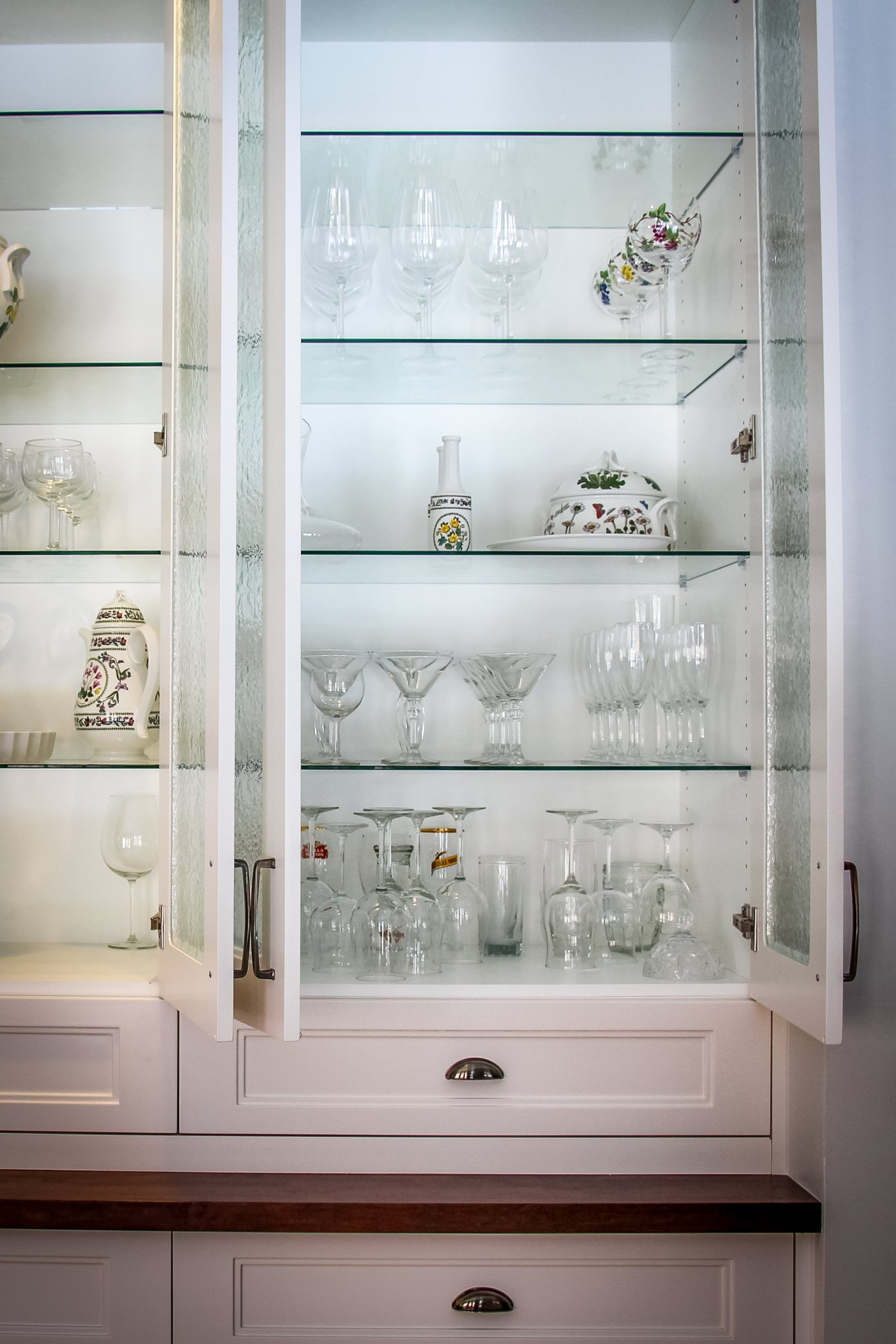 Fine glassware displayed on glass shelves within a builtin china cabinet.