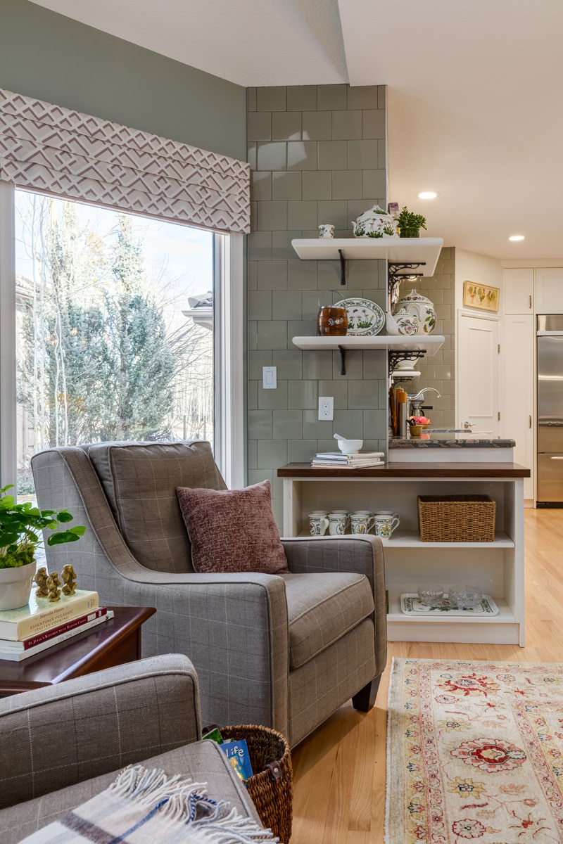 Custom reading chairs in the dining nook in front of a custom wrap-around shelving unit against a full-height glass backslash in a kitchen.