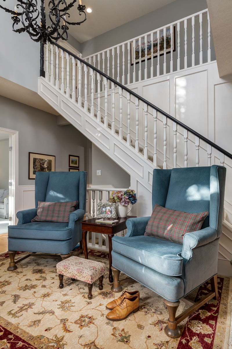 Custom wing back chairs in a deep blue fabric with a footstool and a pair of men's shoes in a traditional entry foyer.