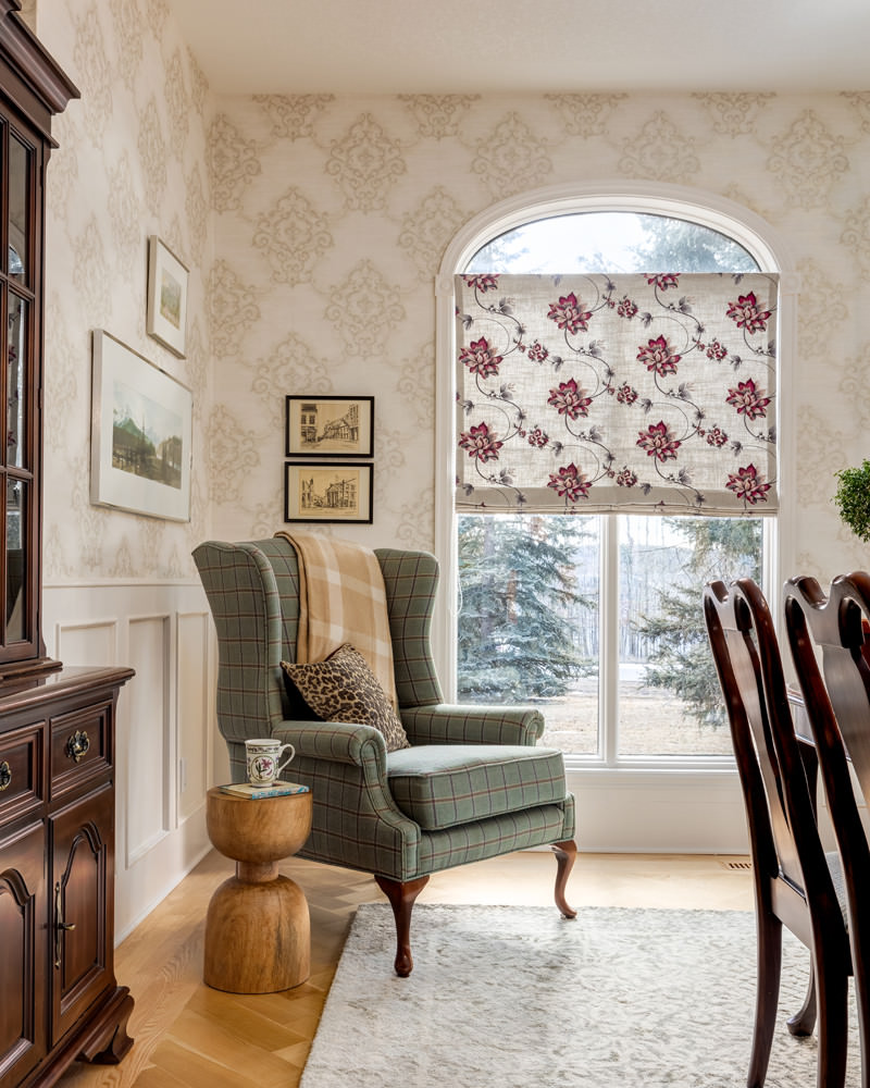 Custom upholstered wingback chair in plaid against patterned wallpaper and window treatments shows patterns working together harmoniously in a single arrangement.
