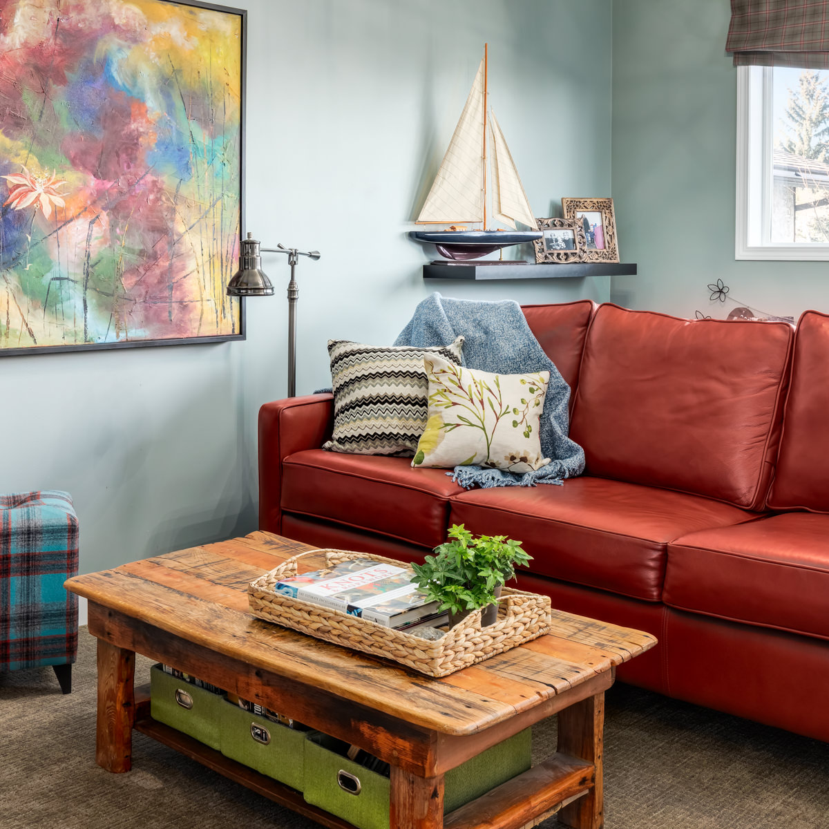 colourful family room with original art, reclaimed wood coffee table and custom leather sofa