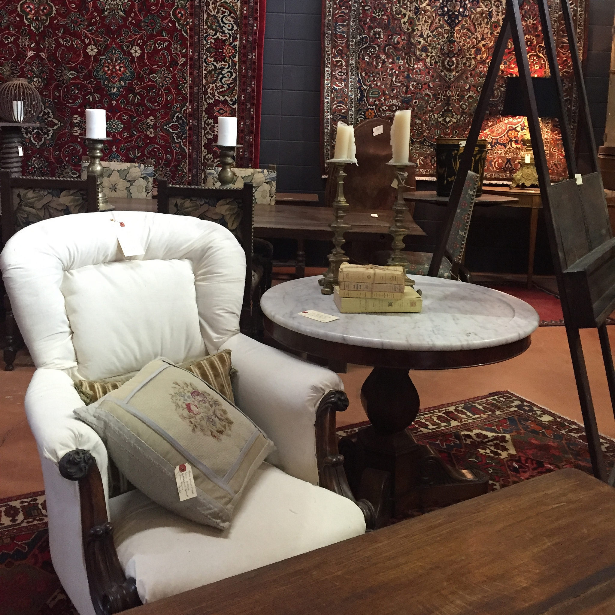 Antique English chair with vintage toss cushion sitting in front of large Persian rugs displayed on wall