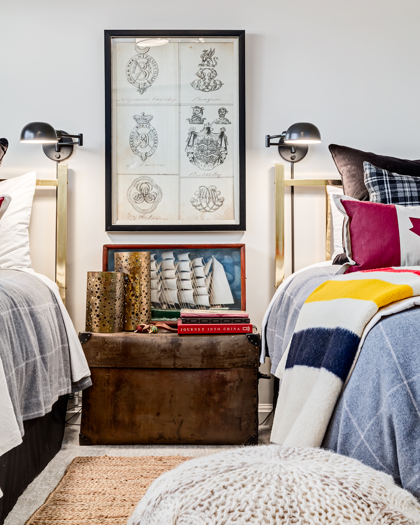 Twin bedroom with brass headboards, wall mounted reading lights and that quintessential Canadian decor item, the Hudson Bay Blanket