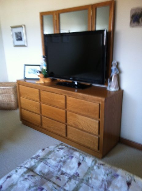 before pics of oak dessert wit black tv on the top in a spare bedroom