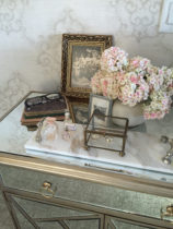 Table scape on mirrored chest features pretty flowers and a vintage family photo