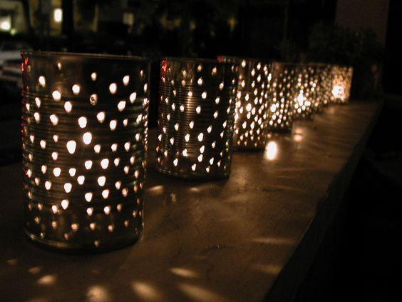 a row of tin can lanterns lit with a tea light