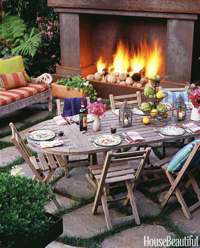 outdoor dining in a rustic setting in front of a blazing fire
