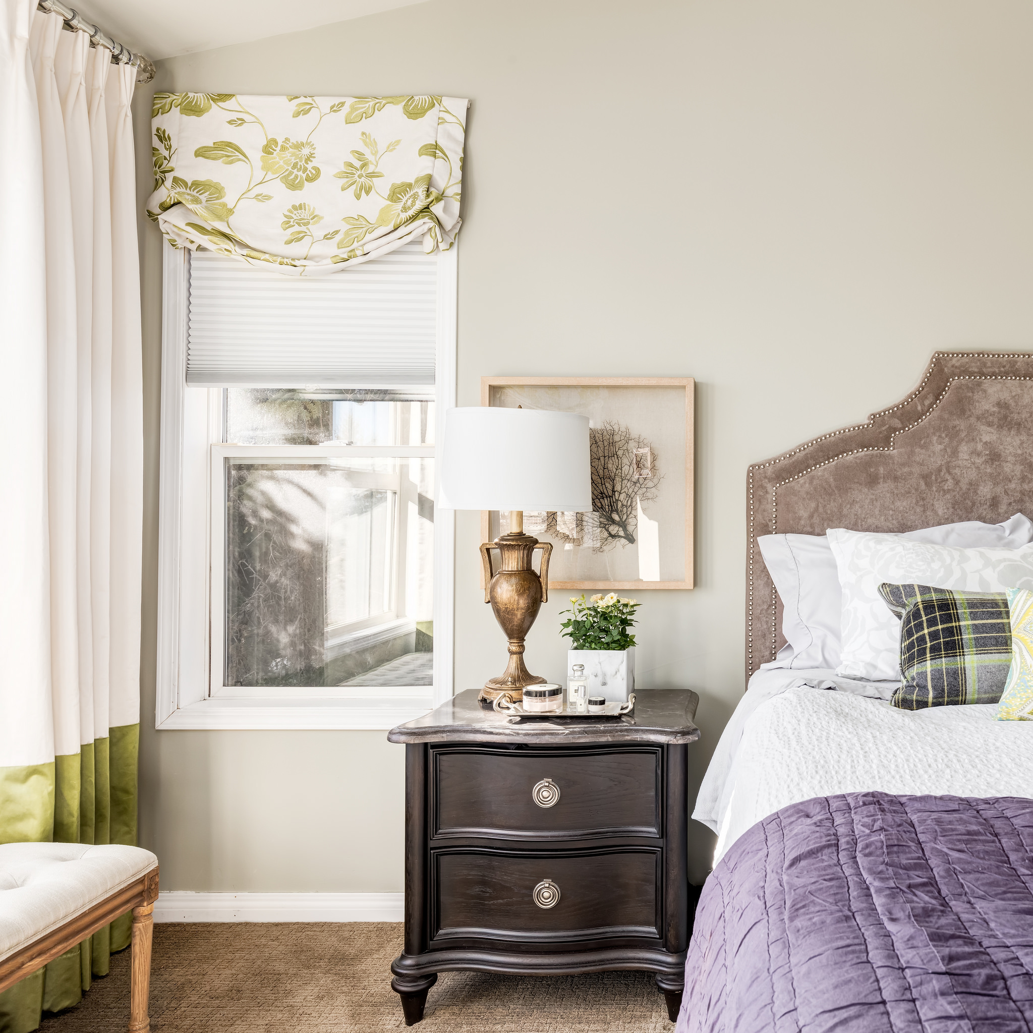 Custom plaid cushion sits on a bed with custom velvet headboard with nailhead detailing. The window coverings are custom and combine floral and plain fabrics.