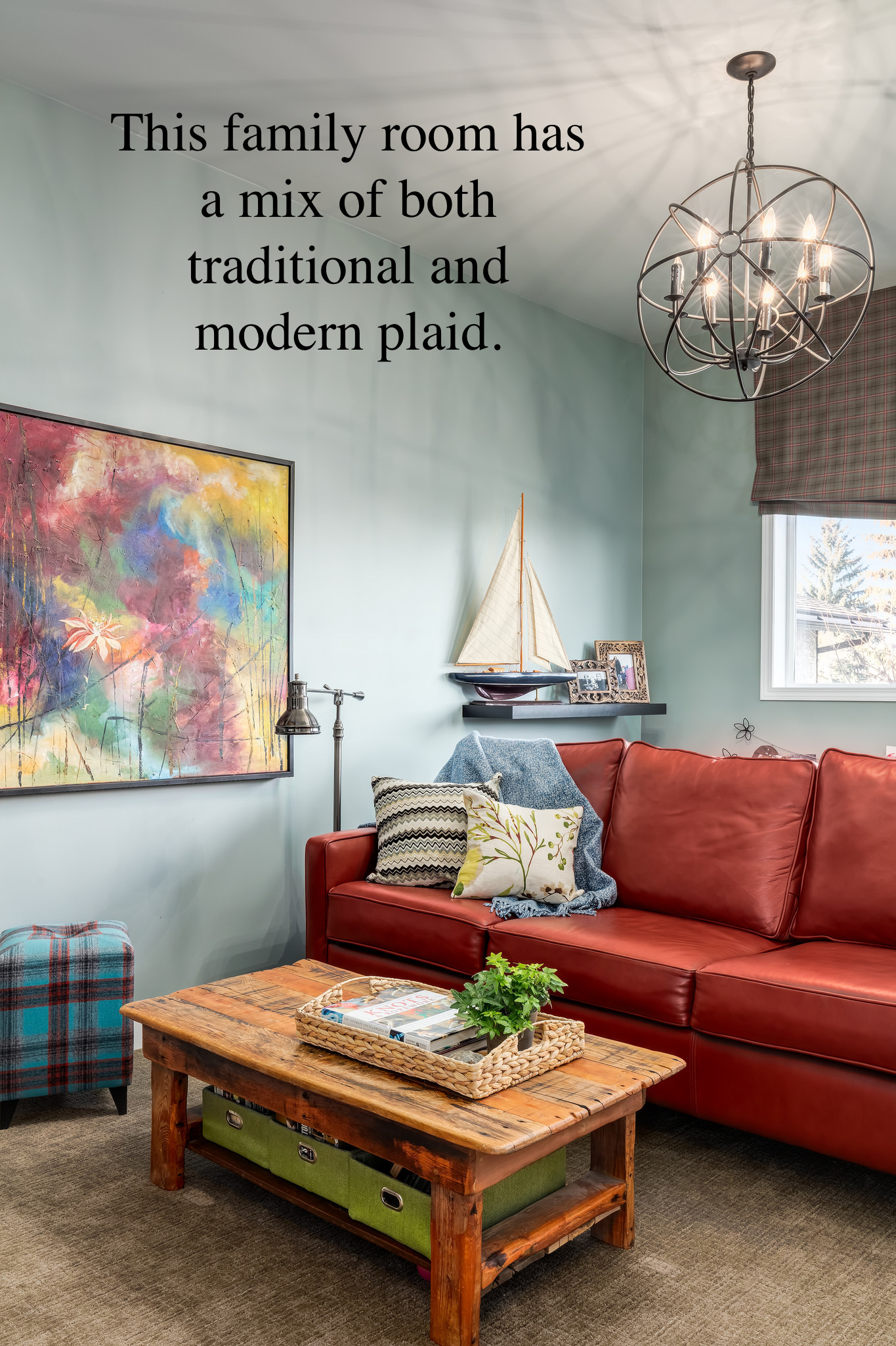 Family room has bright leather sofa that compliments the abstract painting and a colourful plaid stool
