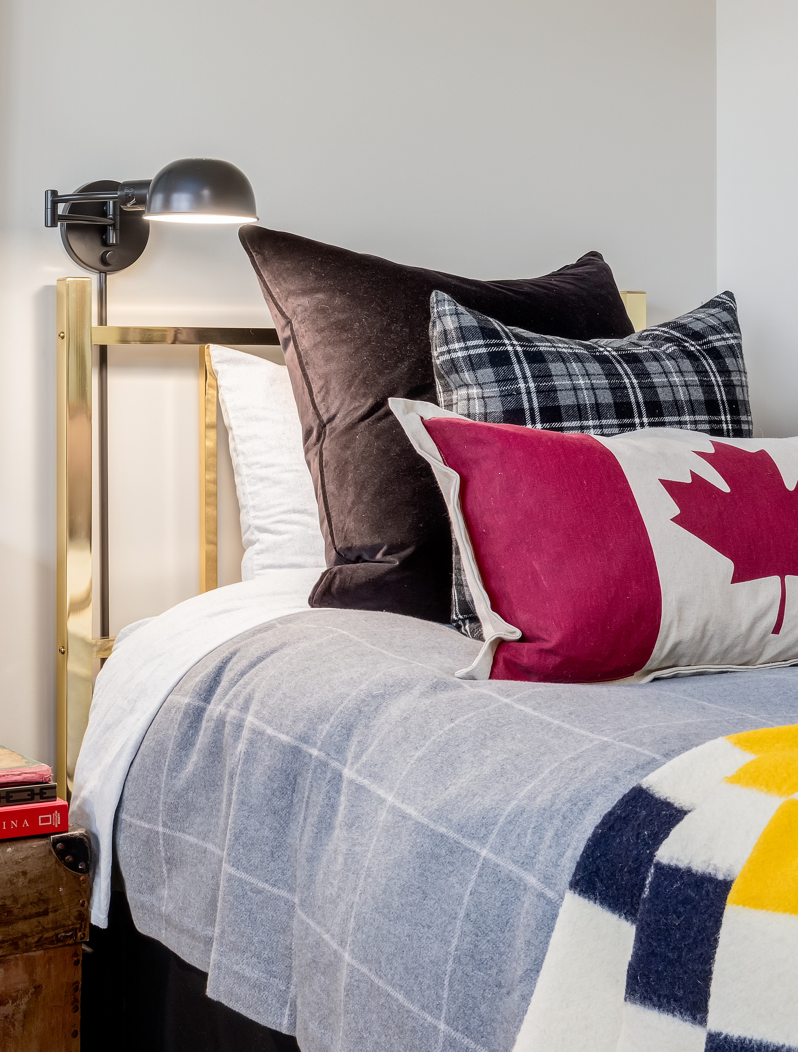 twin guest room has a nod to Canada with Hudson Bay blanket, Canada flag decorator cushion and a few plaids mixed in.