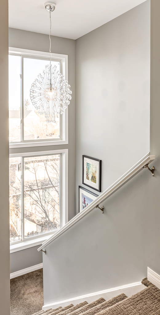 large windows in a stairwell provide a lot of light during day and chandelier gives light during the evening