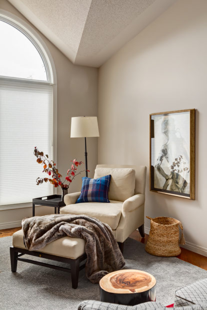 Cream upholstered arm chair in a corner with a footstool and fur throw