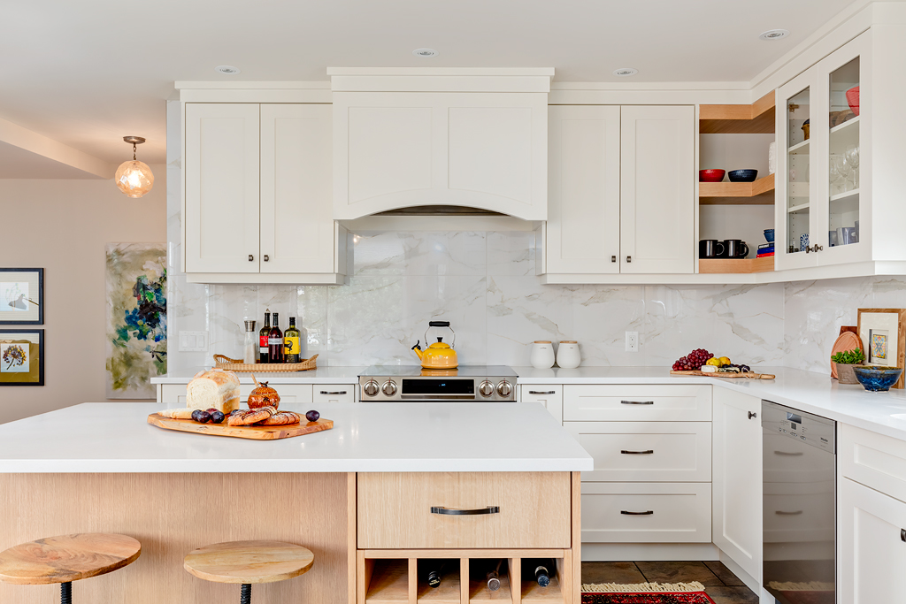 Bright white renovated kitchen with large scale tile backspace and quartz countertops.