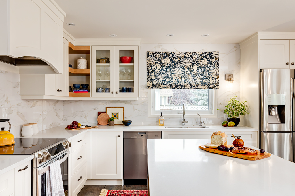 View of remodeled kitchen toward the kitchen sink and window with custom valance and full height marble backsplash.