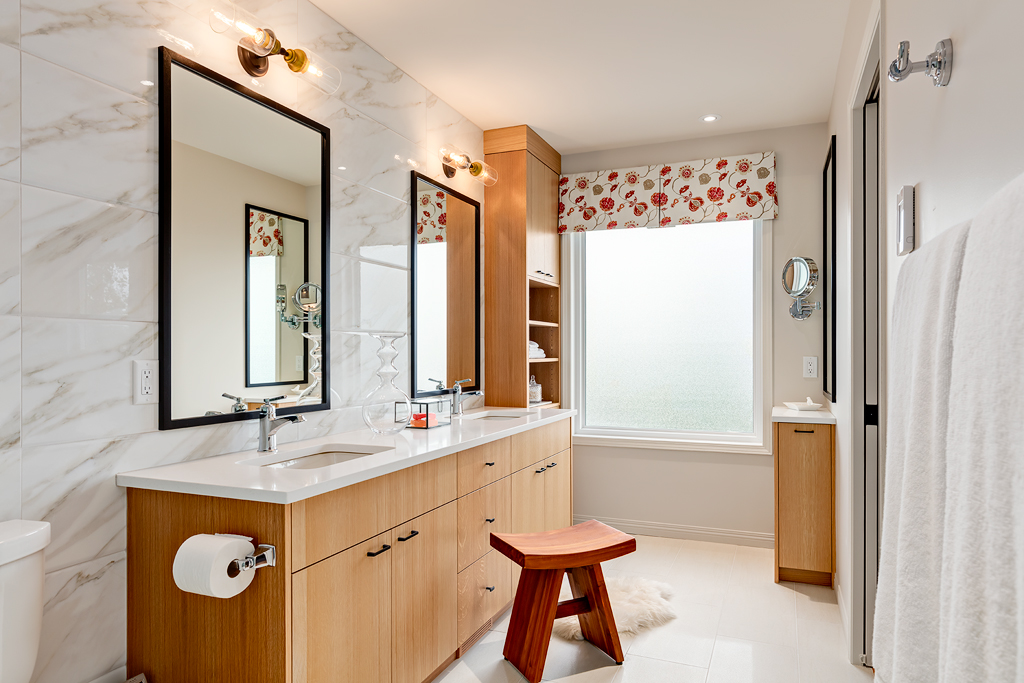 Designer ensuite bathroom with white tile and countertops, and light oak custom built cabinetry including a sideboard cabinet with a clever pull out drawer for curling iron, blow dryer and tall bottles product storage.