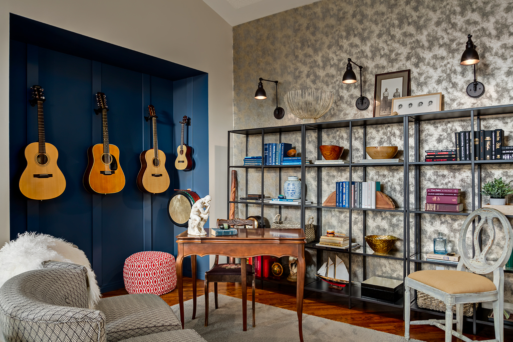 Designer home office with a wall of bookshelves in front of a metallic wallpaper and an alcove of guitars for display.