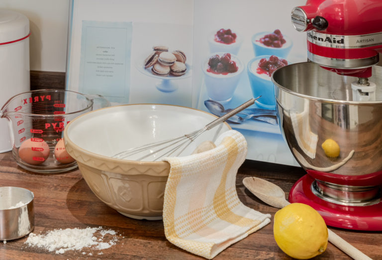 Detail shot of baking supplies including a ceramic bowl, lemon, wooden mixing spoon, eggs, flour, cookbook and red stand mixer.