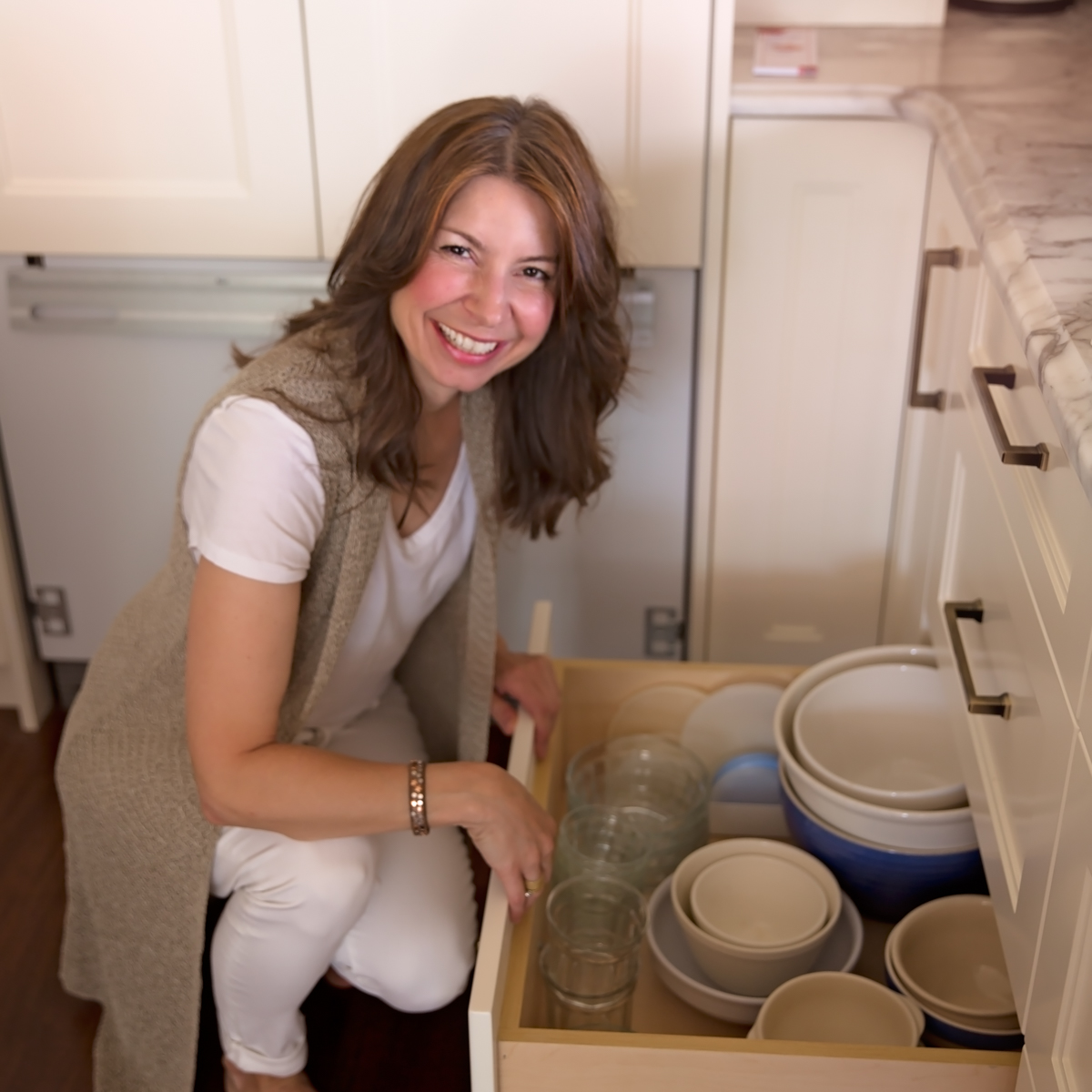A professional organizer works on a kitchen drawer to organize the contents.