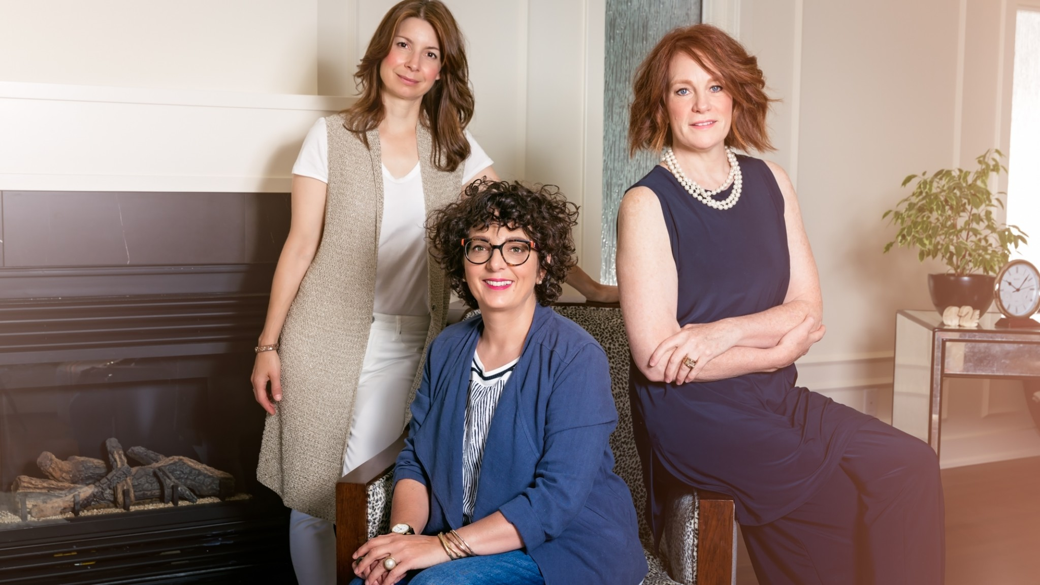 Three interior designers portrait in front of a fireplace.