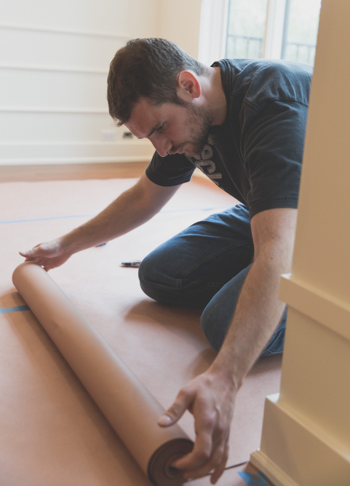 Craftsman preparing for construction work by carefully covering hardwood floors in a home.