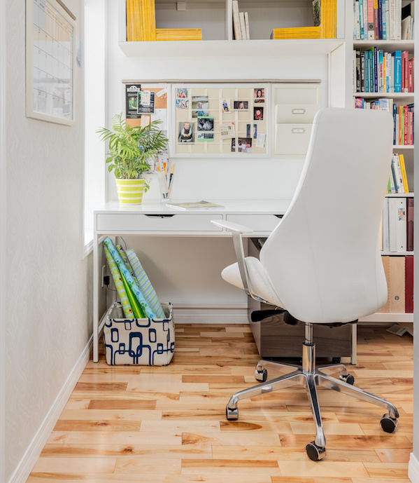 Tall white rolling leather office chair in front of small home office desk surrounded by built-in bookshelves