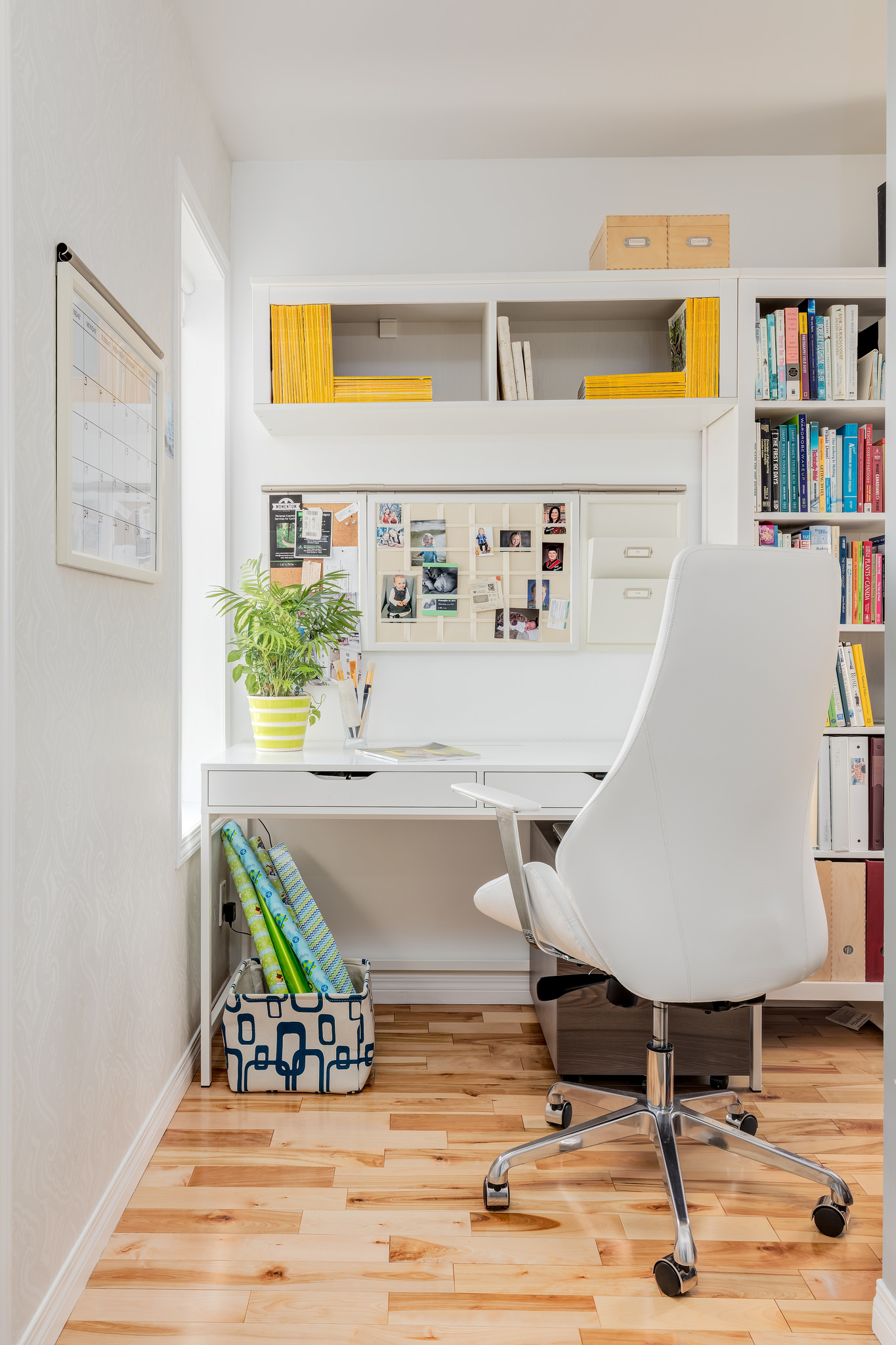 Bright white work area with a rolling white leather office chair, hardwood floors, modern desk and built-in bookshelf surraound, - a great place to work.
