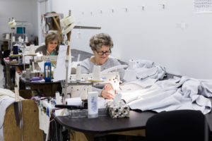 Seamstresses expertly crafting custom draperies.