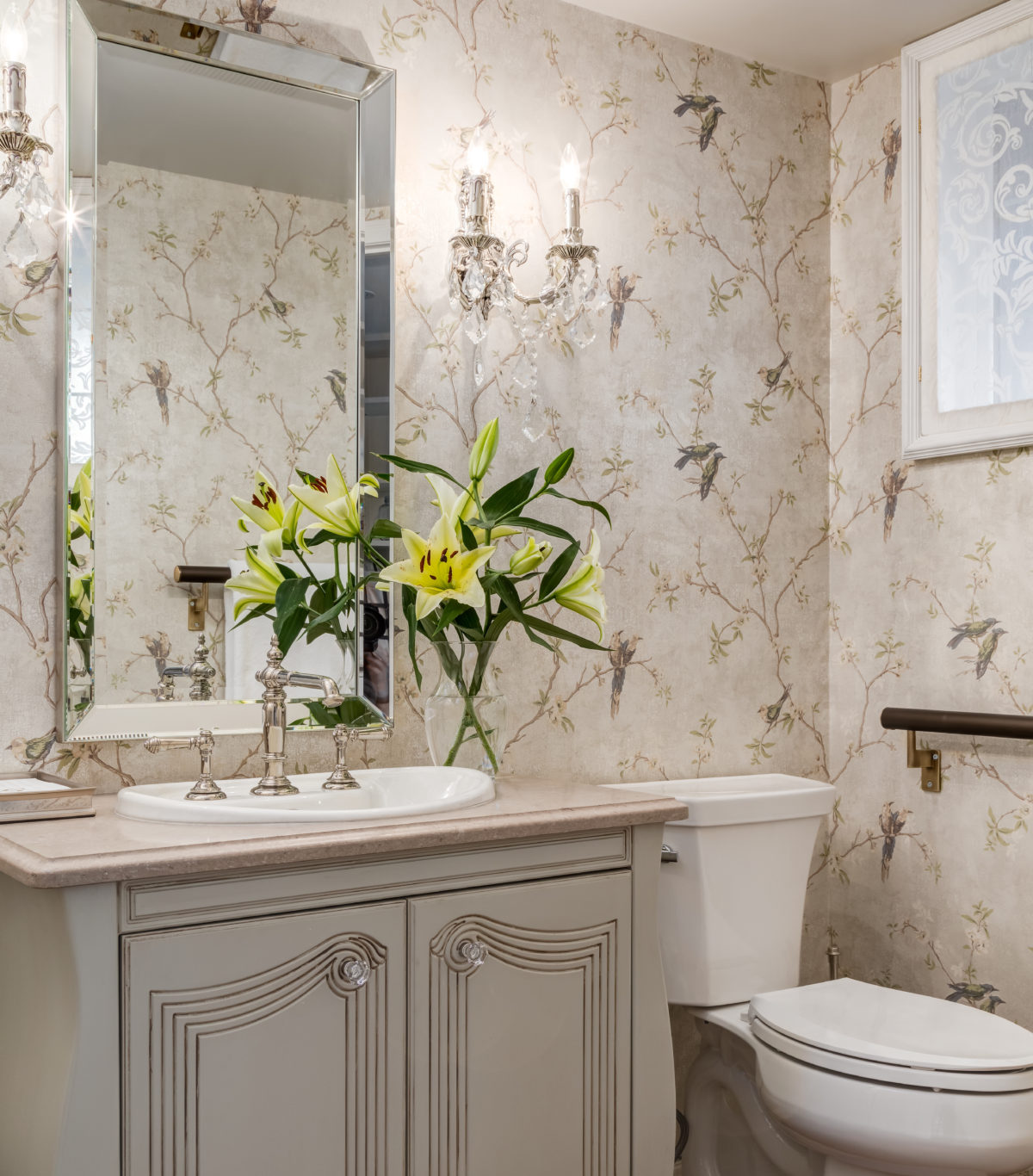 Beautiful designer wallpaper with songbirds in an elegant power room with a restored chest vanity.