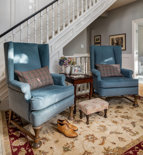 Classic foyer or entryway in a country home with blue upholstered wing back chairs and an antique stool with a white spindle staircase behind.