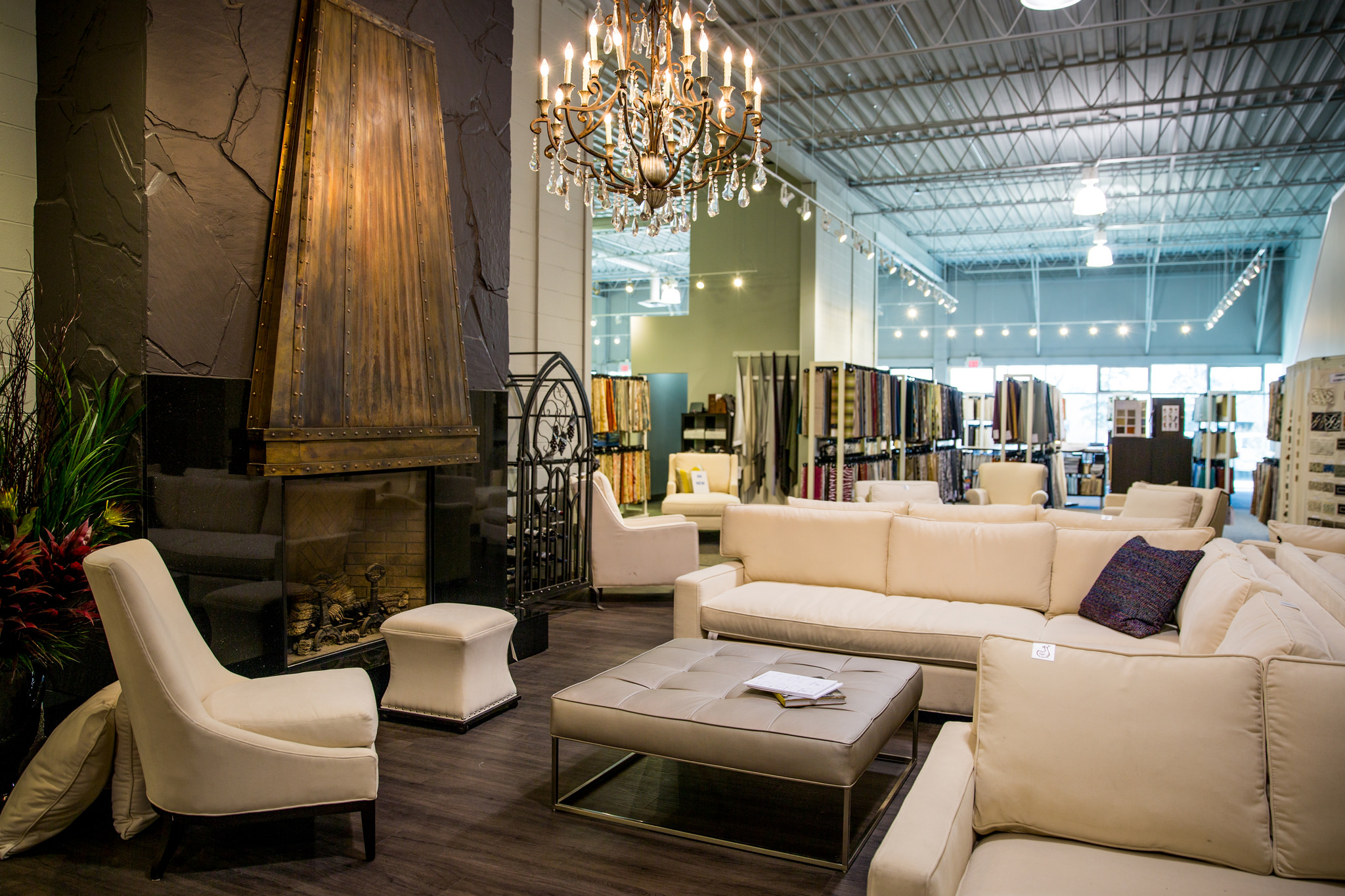 Wide shot of a to-the-trade designer fabric and custom furniture showroom for interior designers with furniture floor models in the foreground and fabric rack sample in the background.