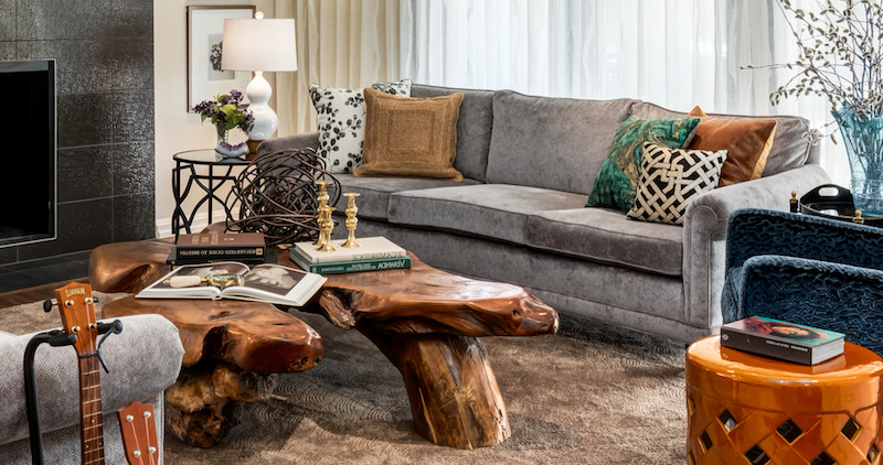 Eclectic living room designed around the owner's existing tree root coffee table with natural textures and fabrics and reupholstered sofa in a light grey velvet.