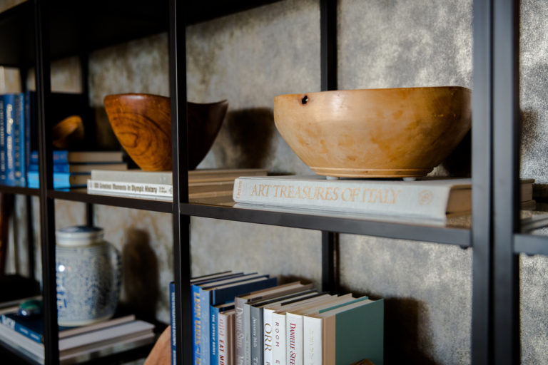 Detail of an iron bookshelf with glass shelves containing books with polished wooden bowls in front of metallic wallpaper.