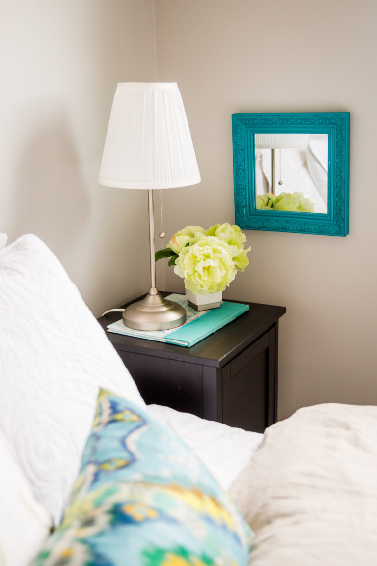 Detail of a side table arrangement in a designer guest room with bright white linens and turquoise accents.