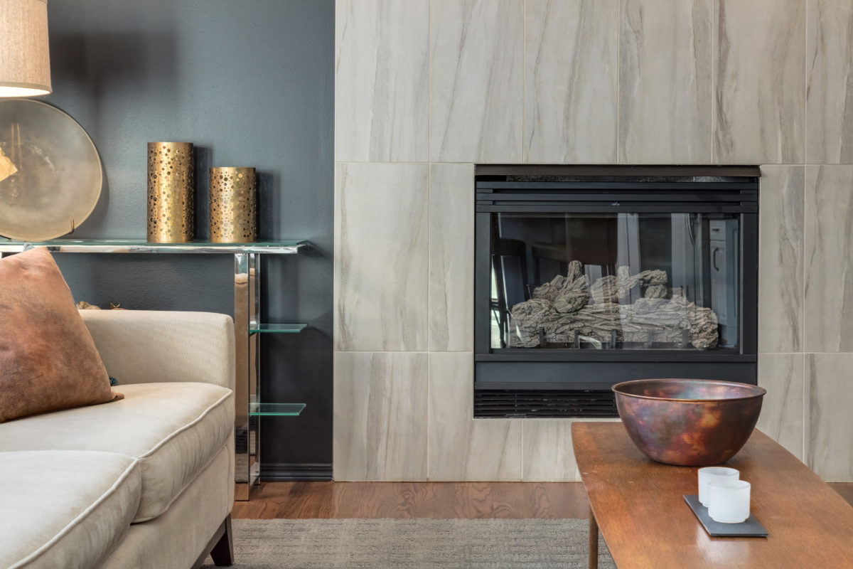 Gorgeous urban modern sophisticated living area with an eclectic mix of mid century and modern furniture pieces around a gas fireplace with large scale porcelain tile surround.