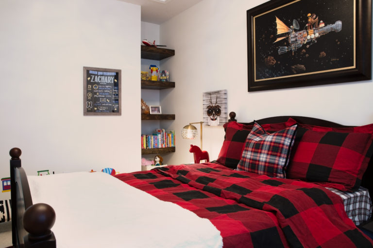 Designer little boy's room with red plaid bedding and playful imaginative artwork with a bookshelf in a nook in the corner.