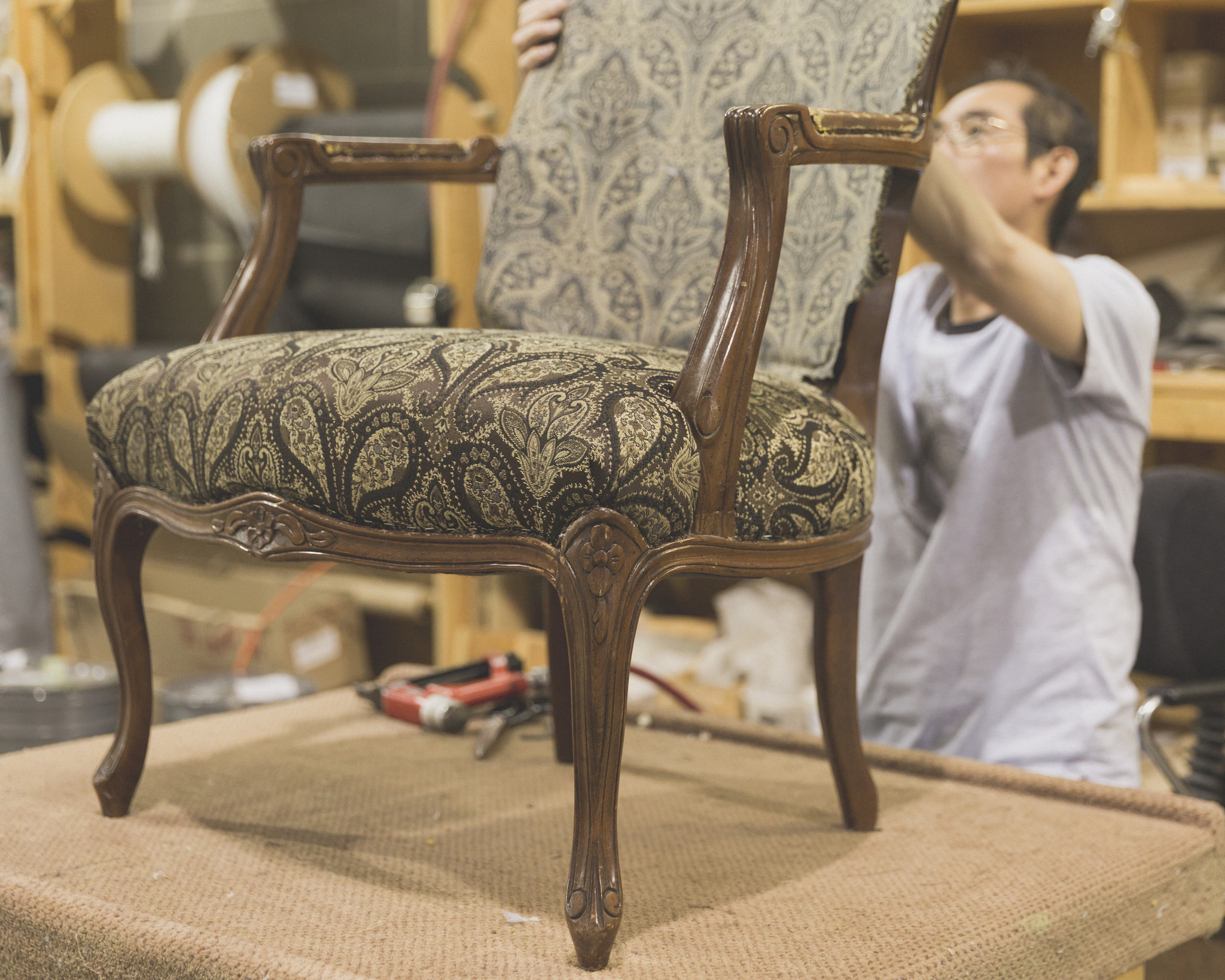 Man works on reupholstering and refinishing vintage arm chair in a designer brocade fabric.