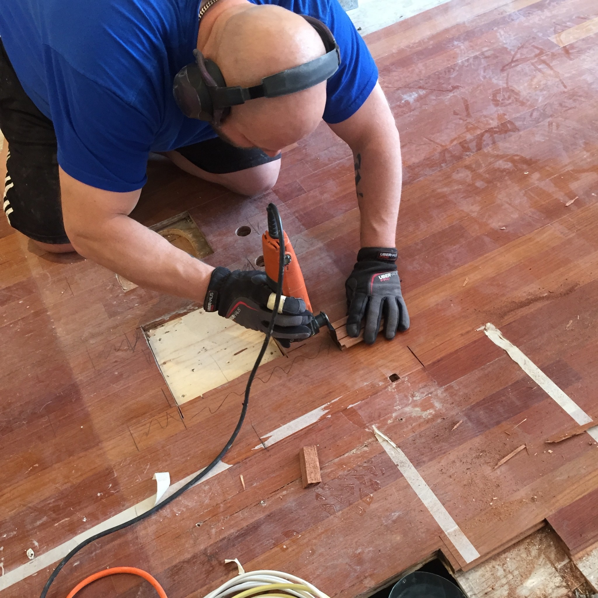 Man repairing a wooden floor with a power tool.